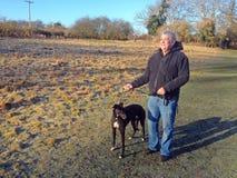 Homme avec le chien de lévrier sur une laisse Photographie stock libre de droits