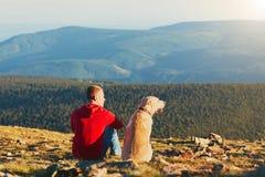 Homme avec le chien en voyage dans les montagnes Images libres de droits