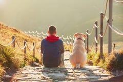 Homme avec le chien en voyage dans les montagnes Photographie stock libre de droits