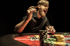 Homme avec le cigare et le verre se reposant à la table de tisonnier et criant photographie stock libre de droits