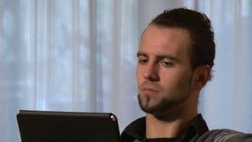 Homme avec le comprimé numérique occupé dans un appel visuel banque de vidéos