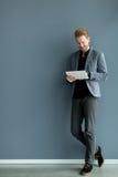 Homme avec le comprimé par le mur Photographie stock