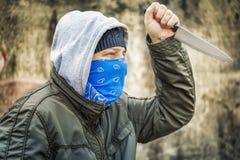 Homme avec le couteau près du vieux mur Photo stock