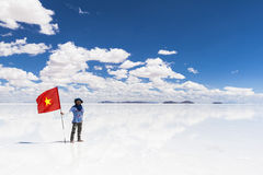 Homme avec le drapeau en Salar de Uyuni, Bolivie Images stock