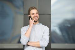 Homme avec le fond urbain de smartphone d'appel de barbe Smartphone heureux d'utilisation de sourire de type pour communiquer des photographie stock libre de droits