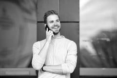 Homme avec le fond urbain de smartphone d'appel de barbe Smartphone heureux d'utilisation de sourire de type pour communiquer des photo stock