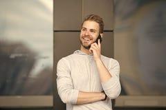 Homme avec le fond urbain de smartphone d'appel de barbe Smartphone heureux d'utilisation de sourire de type pour communiquer des photo libre de droits