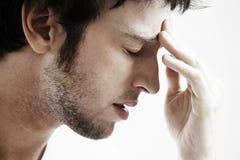Homme avec le front émouvant de mal de tête Image stock