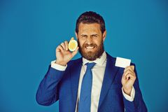 Homme avec le fruit aigre de citron, tenant les affaires ou la carte de crédit images libres de droits