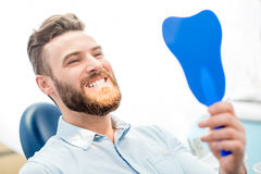 Homme avec le grand sourire au bureau dentaire photographie stock libre de droits