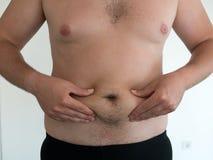 Homme avec le grand ventre sur le fond blanc Photo stock
