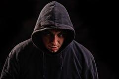 Homme avec le hoodie ou le voyou au-dessus du fond foncé Image stock