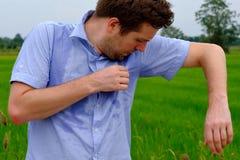 Homme avec le hyperhidrosis suant très mal sous l'aisselle dans la chemise bleue, d'isolement sur le gris images stock