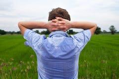 Homme avec le hyperhidrosis suant très mal sous l'aisselle dans la chemise bleue, sur le gris images libres de droits