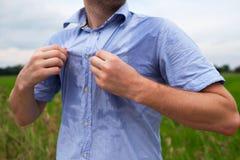 Homme avec le hyperhidrosis suant très mal sous l'aisselle dans la chemise bleue, sur le gris image stock