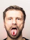 Homme avec le jujube sur la langue Image stock