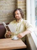 Homme avec le livre de lecture de tasse de café en café Image libre de droits