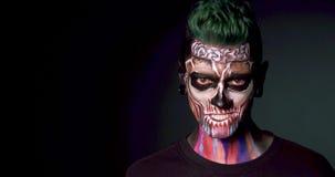 Homme avec le maquillage coloré de crâne montrant le sourire mauvais banque de vidéos