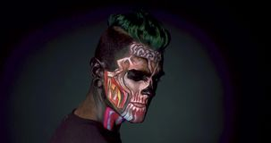 Homme avec le maquillage squelettique coloré clignant de l'oeil à l'appareil-photo banque de vidéos