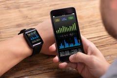Homme avec le mobile et le taux de battement de coeur d'apparence de Smartwatch images stock