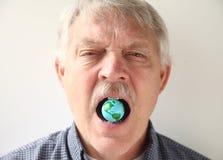 Homme avec le modèle de la terre dans sa bouche Photos stock