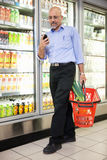 Homme avec le panier et le téléphone portable d'épicerie Images libres de droits