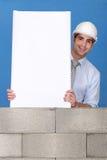 Homme avec le panneau blanc sur le mur Photo stock