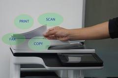 Homme avec le papier sur l'imprimante fonctionnelle multi à imprimer, balayer, copier et envoyer par fax dans le bureau photographie stock
