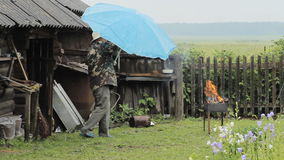 Homme avec le parapluie près du feu pour le barbecue La pluie tombe, un vieux bâtiment avec une barrière à l'arrière-plan banque de vidéos
