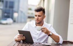 Homme avec le PC et le café de comprimé au café de ville photos libres de droits