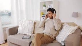 Homme avec le PC et les écouteurs de comprimé à la maison banque de vidéos