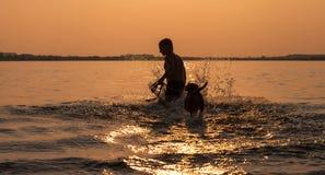 Homme avec le petit chiot de briquet dupant autour dans la vague de coucher du soleil d'océan Images stock