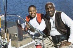 Homme avec le petit-fils dans un bateau Photo stock