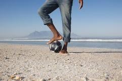Homme avec le pied sur le ballon de football à la plage Photos libres de droits