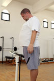 Homme avec le poids excessif sur des échelles dans le gymnase Image libre de droits