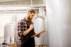 Homme avec le presse-papiers à la brasserie de métier ou à l'usine de bière Image libre de droits