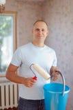 Homme avec le rouleau de peinture Image stock