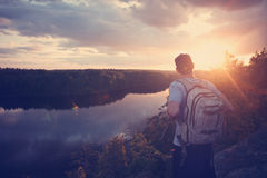 Homme avec le sac à dos et le chapeau sur la falaise au-dessus de la rivière et du regard loin Photos libres de droits