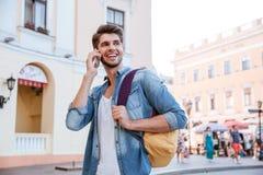 Homme avec le sac à dos parlant au téléphone portable dans la ville photo stock