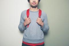 Homme avec le sac à dos rouge sur le fond vert et blanc Photos stock