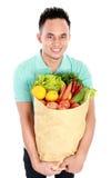 Homme avec le sac de papier plein des fruits et légumes photographie stock libre de droits