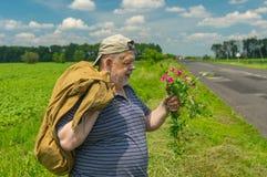 Homme avec le sac et le groupe de fleurs sauvages se tenant sur un bord de la route en Ukraine centrale Photo stock