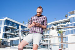 homme avec le service de mini-messages skateboar sur le smatphone Image stock
