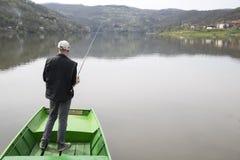 Homme avec le sien de retour vers la pêche d'appareil-photo de la ficelle tournoyante de bateau et des poissons de attente pour p Photo libre de droits