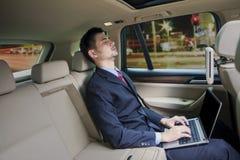 Homme avec le sleepin d'ordinateur portable dans une voiture photographie stock