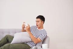 Homme avec le smartphone étant étonné en tant que jouer des jeux images stock