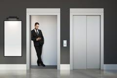 Homme avec le smartphone dans l'ascenseur Photographie stock libre de droits
