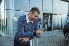 Homme avec le smartphone devant la façade en verre image stock