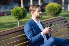 Homme avec le smartphone en parc Directeur avec le téléphone portable sur extérieur ensoleillé L'homme d'affaires dans le costume Image stock