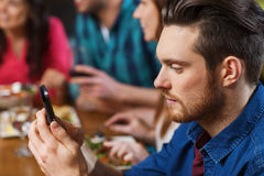 Homme avec le smartphone et les amis au restaurant Image libre de droits